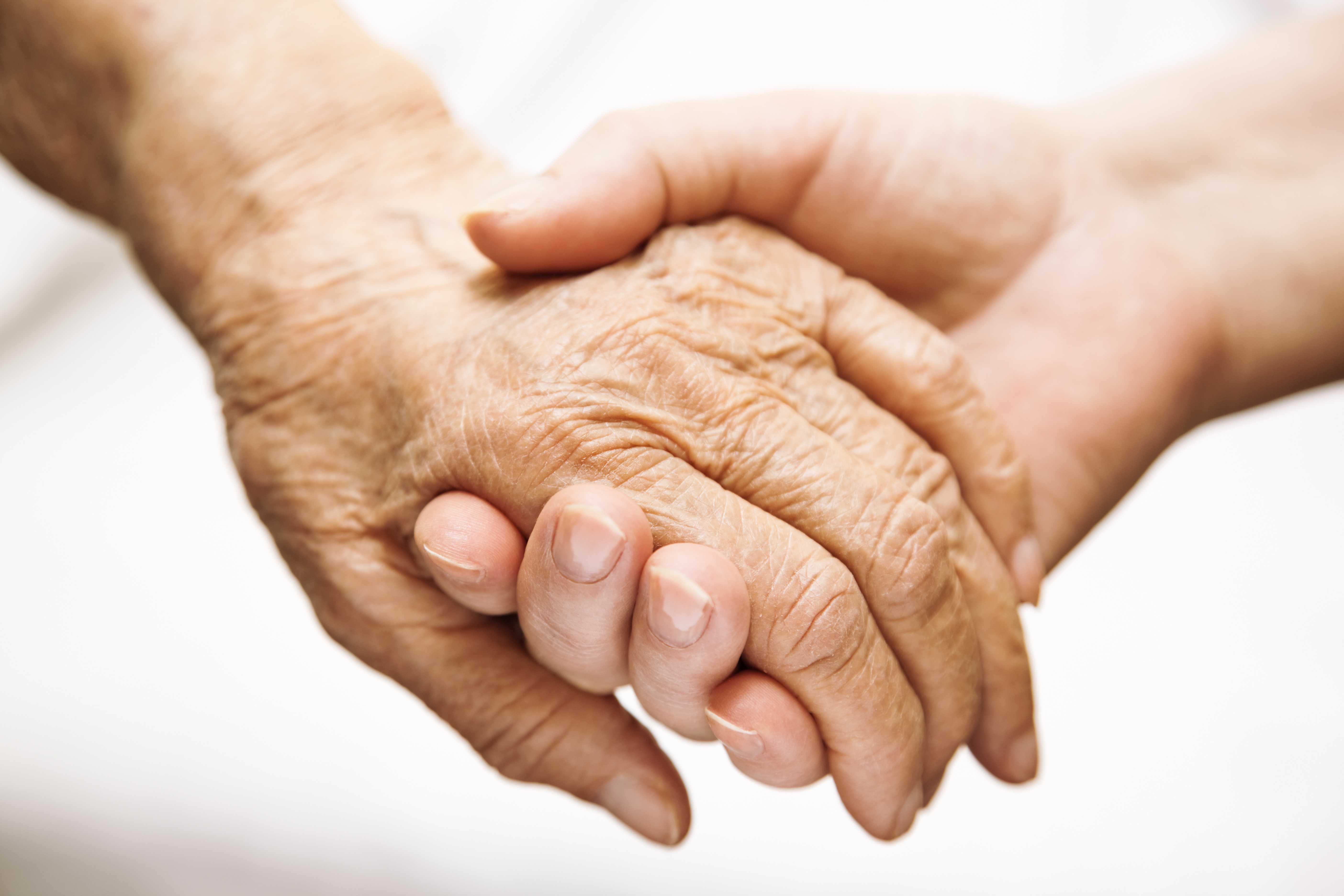 Junger Mensch nimmt Senior an die Hand