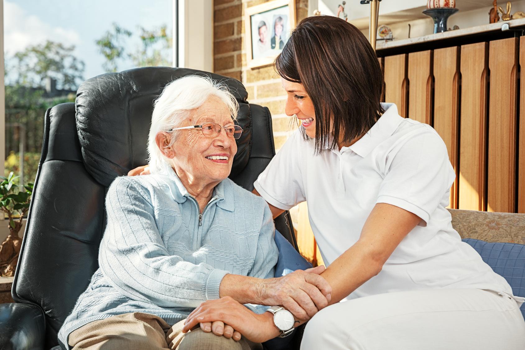 Pflegerin-sitzt-bei-Seniorin
