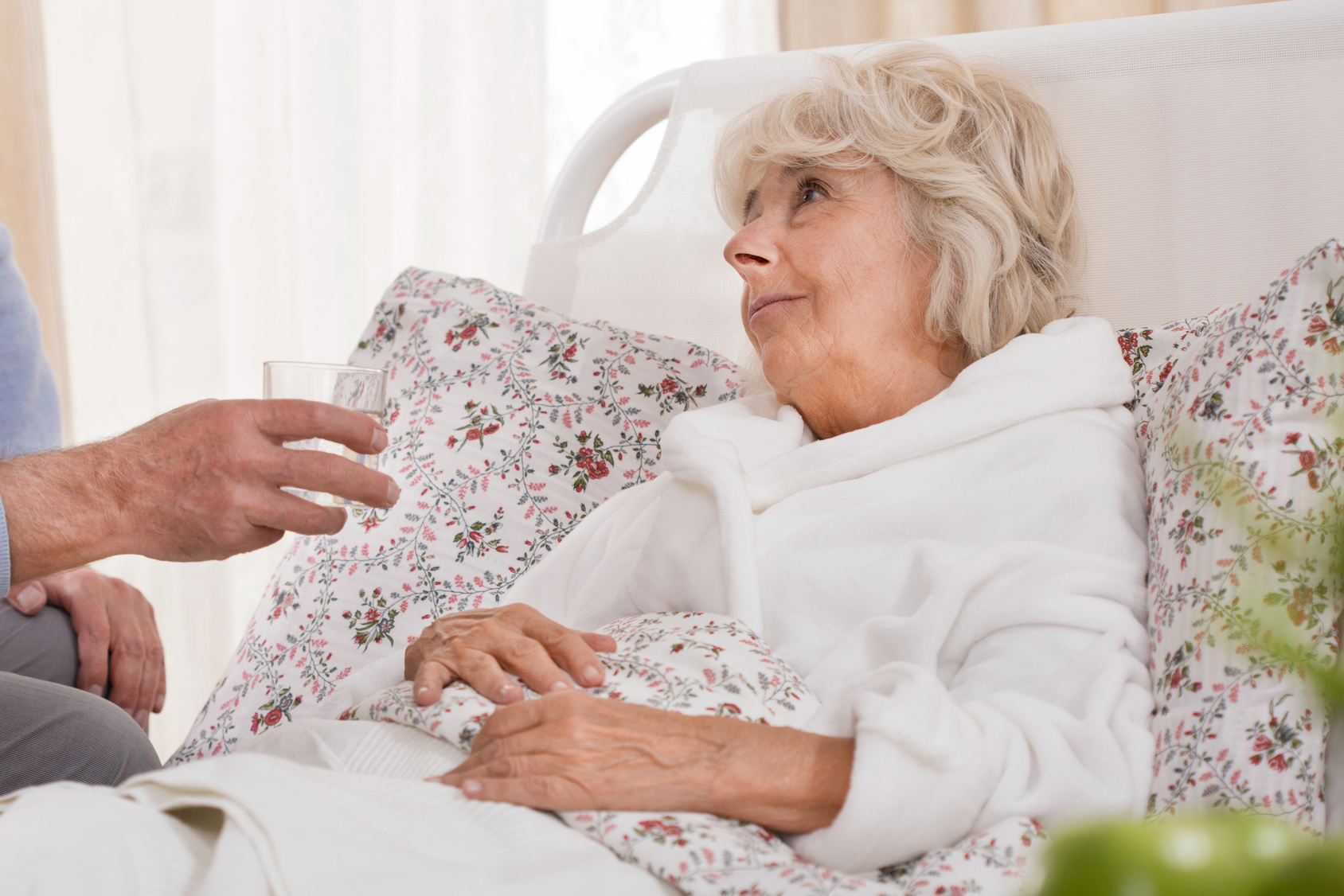 Seniorin mit Parkinson im Bett